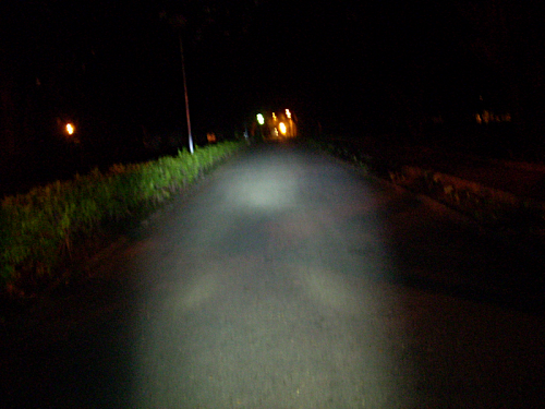 Bicycle headlamp IXON IQ on a dark narrow road