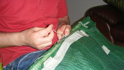 Homem a coser cortinado de rede sombreira com ponto cruz