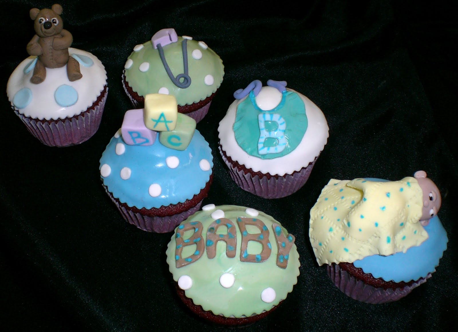 baby shower cupcakes featuring a sleeping baby teddy bear bib safety