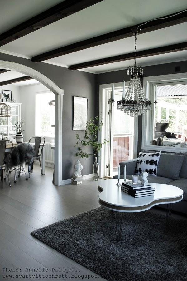 magnoliakvist, skulptur, vit, vitt, vitt golv, treklöver bord, furniturebox, gråa väggar, grå färg på vägg, vardgsrum, valv mellan rum, vitmålade snickerier, bruna takbjälkar, matplats, matstolar, matbord, fårskinn, inredning, grå tygsoffa, vitt soffbord, grå matta, golv, fönster, altandörr, batikkudde, lagerhaus, böcker på bordet som dekoration, ljus, stor flaska för blommor