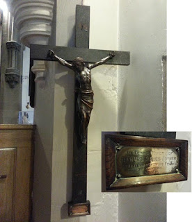 A cruxifix in bronze or brass on wood.  It is hanging on a white painted pillar in a church which can just be glimpsed behind.  There is an inset picture of the detail of the dedication plaque at the cross's foot.
