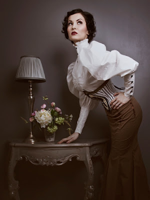 A woman clad in Neo-Vicotrian garb leans against a beautiful end table against a grey backdrop.