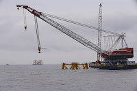 In this July 27, 2015, file photo, the first foundation jacket installed by Deepwater Wind in the nation's first offshore wind farm construction project is seen next to a construction crane on the waters of the Atlantic Ocean off Block Island, R.I. (Credit: AP Photo/Stephan Savoia, File) Click to Enlarge.