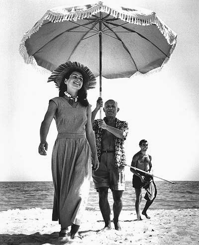 Picasso hold a parasol over his muse Francoise Gilot on the sandy beach