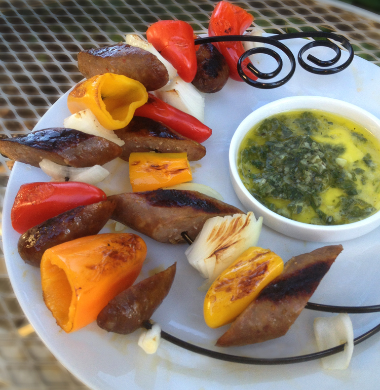 Image of circle kabobs with mini red, yellow and orange peppers, sweet onions and sliced sausage. They are served on a white plate with sweet basil dipping sauce in a separate dish.