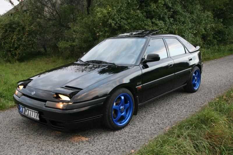 Mazda Astina, Familia, 323F BG, popularny samochód, dla młodego, ciekawy design, otwierane reflektory, czarny, niebieskie felgi, zdjęcia