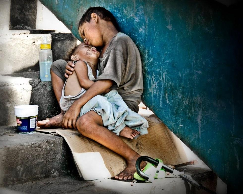 Niño de la calle protegiendo a su hermana pequeña. Manila, Filipinas. Fotógrafo: Mio Cade.