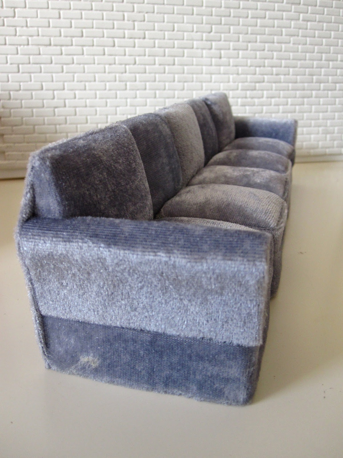 Modern miniature five seater grey velvet sofa.