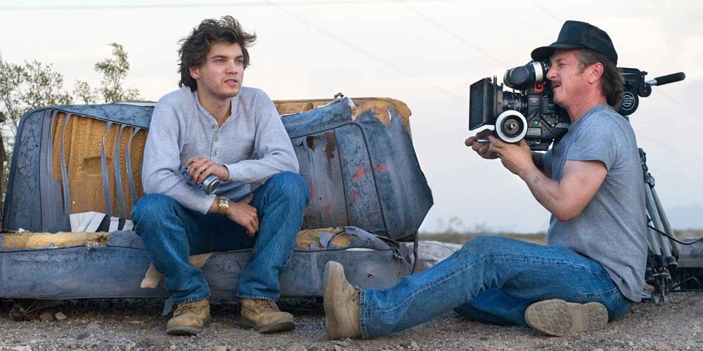 Sean penn como diretor de cinema operando uma câmera cinematográfica no set do filme into the wild enquanto filma uma cena com o ator Emile Hirsch sentado em um sofá a beira de uma estrada