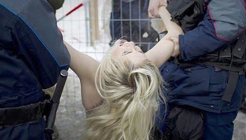 Dua orang petugas membawa pakasa wanita bugil ini