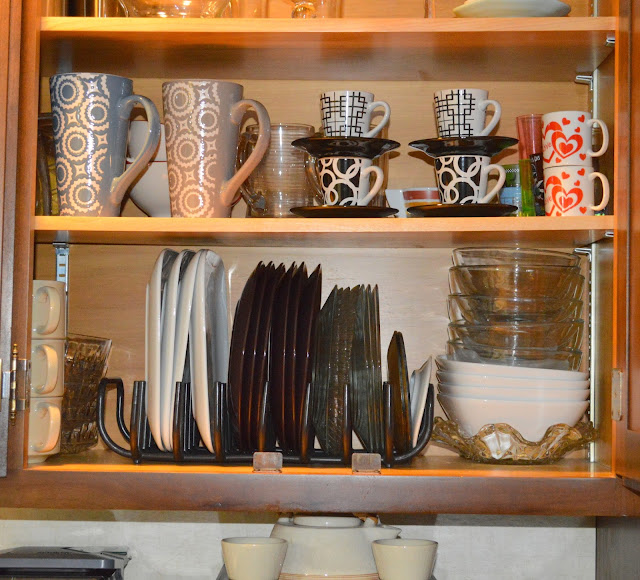 using a dish drainer to hold the dishes up right in a cabinet
