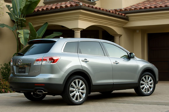 Rear 3/4 view of silver 2011 Mazda CX-9 in front of home
