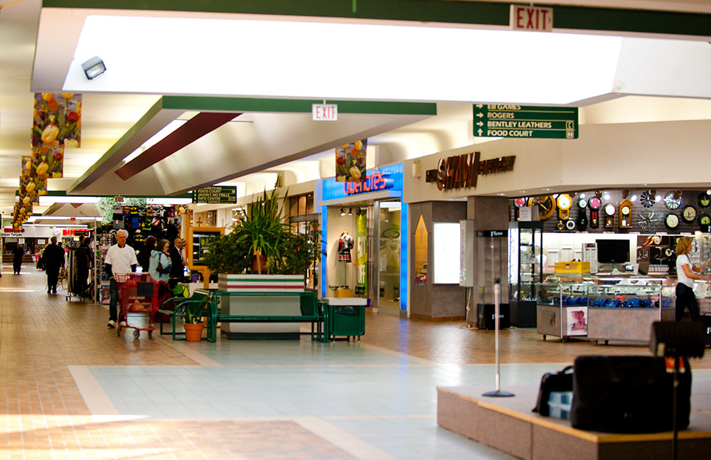 A view of the interior of the Orillia Square Mall with an event in the process of being set up, while early shoppers stop to watch.