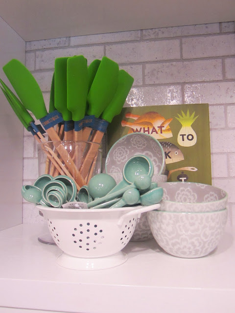 Close up of mint measuring spoons, green spatula and grey ceramic bowls with white flowers