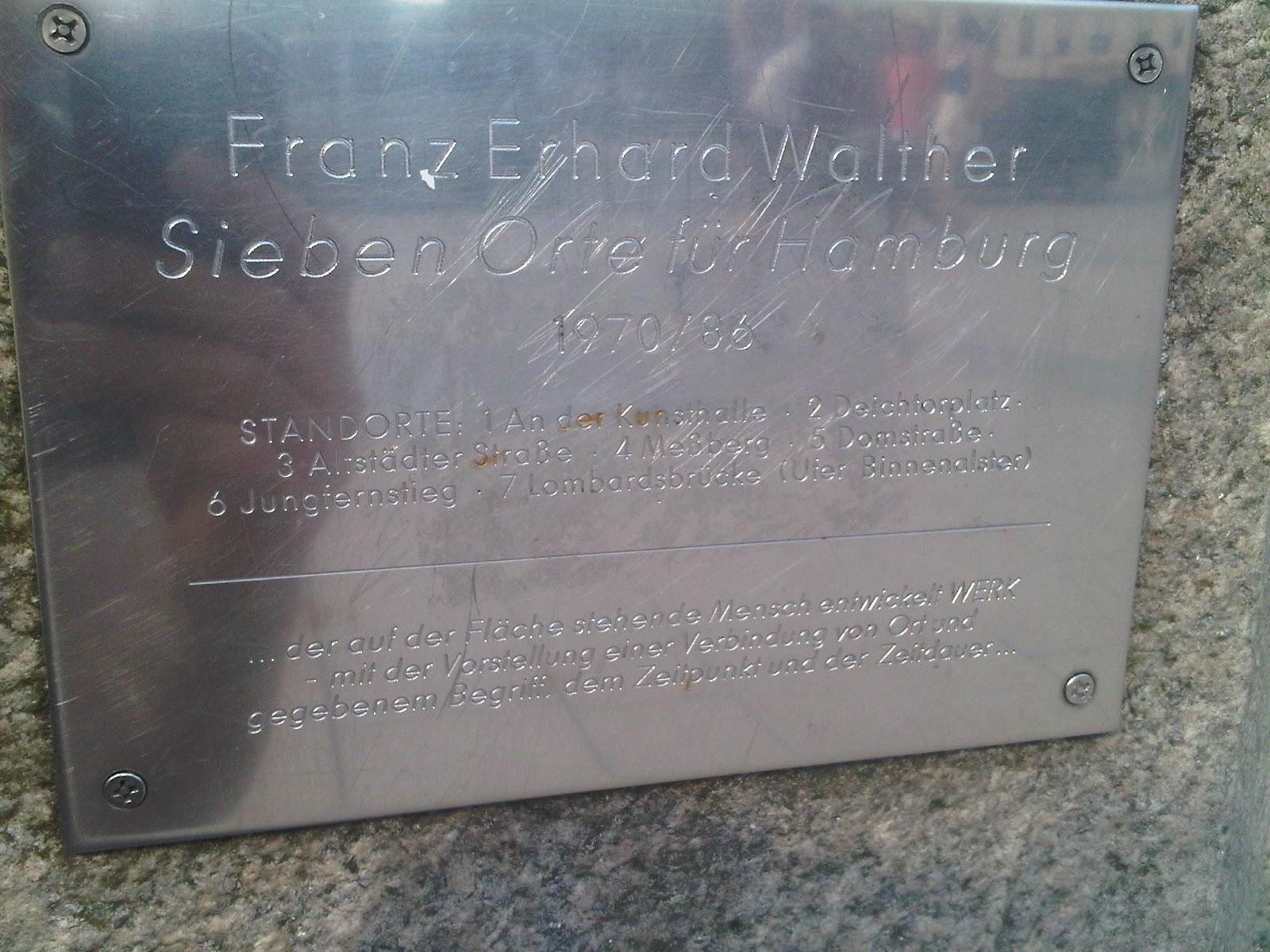 Sieben Orte für Hamburg - Franz Erhard Walther - Hinweistafel für eine Metallplatte auf dem Gehweg des Jungfernstieges