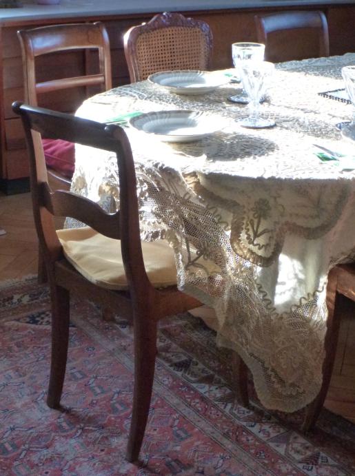 Eine Tafel mit Spitzendecke und Kristallgläsern, auf der die Sonne ruht. Um den Tisch herum stehen alte Holzstühle, auf dem Boden liegt ein Perserteppich.