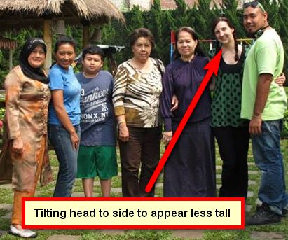 Tall person next to a bunch of short people, tilting head to appear less tall