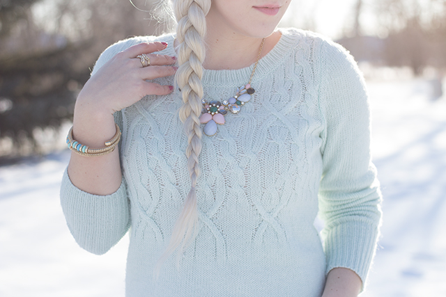 Statement necklace with mint blue cable knit sweater.