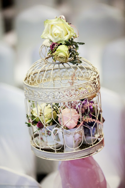 vintage themed wedding decoration bird cage filled with vintage cups and saucers and flowers