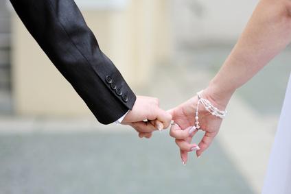 חתן וכלה מחזיקים באצבעות