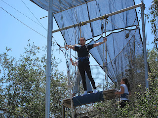 Noah grabbing the fly bar on the flying trapeze platform.