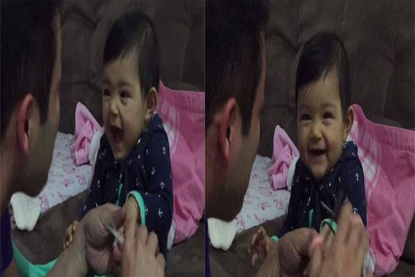 Adorable baby pretends to cry as dad cuts her fingernails - but ends up laughing instead