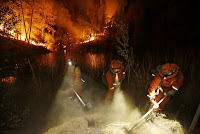 Firefighters create a firebreak near a home in Middletown, Calif., on Sunday, Sept. 13, 2015. (Credit: AP Photo/Elaine Thompson) Click to Enlarge.