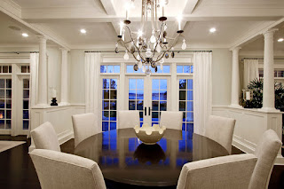 Traditional White Chairs around the Round Dining Tables under Wide Iron Chandelier and the White Ceiling