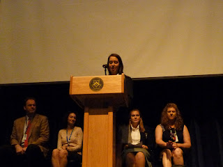 Photo of our Head SLP Elizabeth speaking at the podium while Hugh, Christina, Keebler and I are sitting in the background.