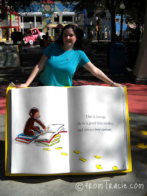 Tracie standing behind a giant Curious George Book
