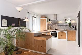 Landhausküche mit sanfter Beleuchtung unter den weissen Boarden,, einer Stehlampe und einzelnen Spots im Arbeitsbereich