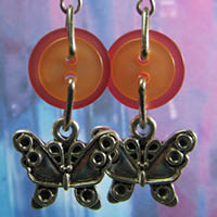 Butterfly charm earrings have silver lucky charms hanging from layered orange buttons