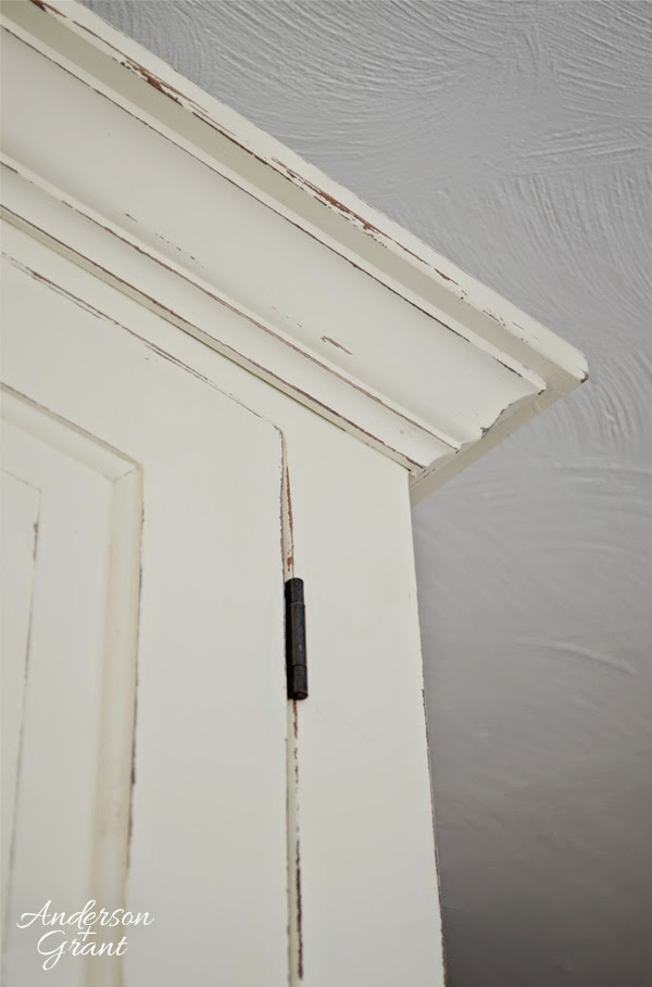Distressed finish on painted wood pantry cupboard | www.andersonandgrant.com