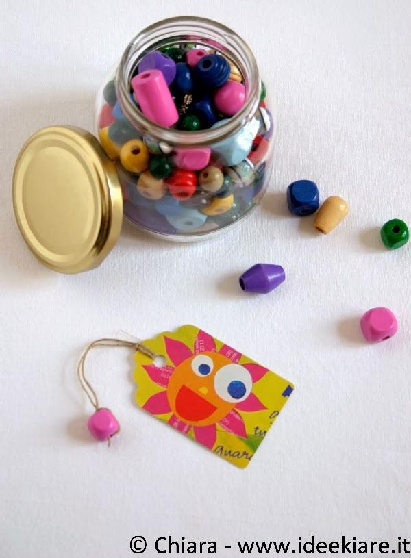 fare un segnalibro con ritagli di giornale, spago e perla di legno