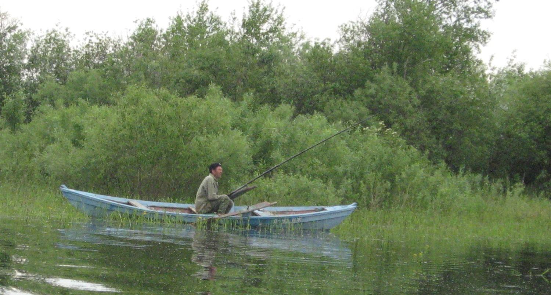 Любитель рыболов с удочкой на лодке
