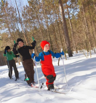 3 kids nordic skiing in line from youngest to oldest through the sunny woods.