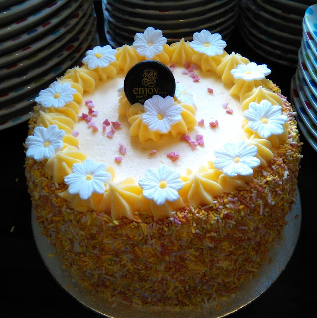 lemon butter cream cake with colourful sprinkles and white daisies