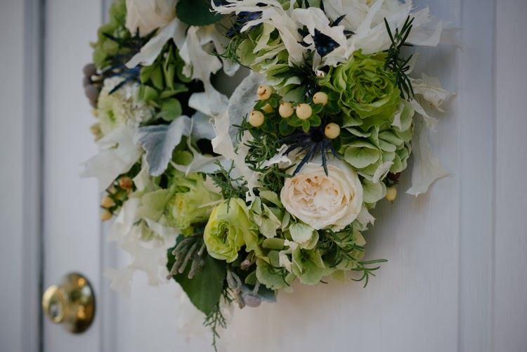 wedding wreath on front door with green and white roses