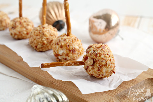 These Mini Honey Roasted Almond Cheese Balls are a creamy mixture of mozzarella, Parmesan, & cream cheese that are rolled in sweet & crunchy honey roasted almonds and served on a pretzel stick.