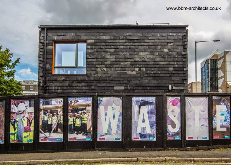 Valla de la construcción y una de las fachadas de la casa ecológica inglesa proyecto sustentable reciclando basura