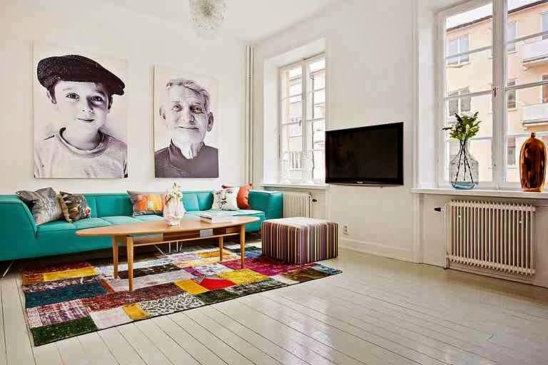 Turkusowa kanapa, kolorowy dywan,białe wnętrze z kolorami, portrety na ścianie, niebieska butelka na parapecie