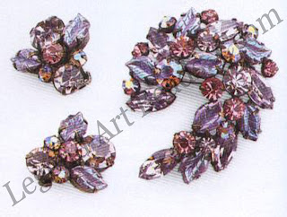 """In this brooch and earring set by Regency, known for their interplay of hues and textures, lilacs mix with light amethysts and leaf-shape stones with an """"Aurora Borealis"""" sheen, all hand-set in dark-coated prong settings. Mid-195os"""
