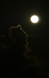 Moon at night shining on clouds
