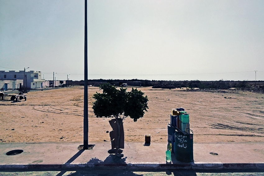 Foto de um posto de venda de gasolina na beira da estrada, composto por apenas alguns bidões e latas