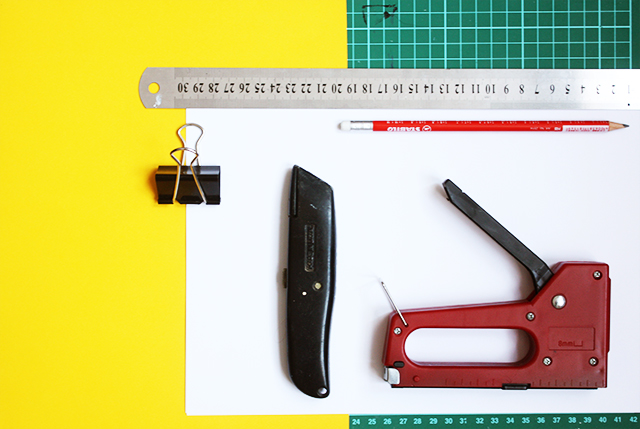 supplies for making a notebook laid out, stapler, stanley knife, bulldog clip, ruler and paper