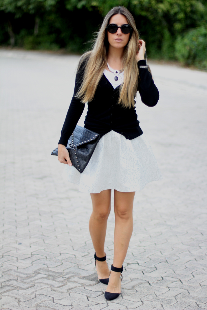 Fashion blogger wearing silver skater skirt and studded clutch