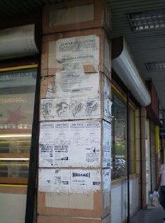 Posting ads on building wall in Kampung Air area Kota Kinabalu