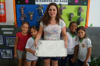 A professora Lívia Lagreca apresenta seu tabuleiro de cuscuz feito com os alunos