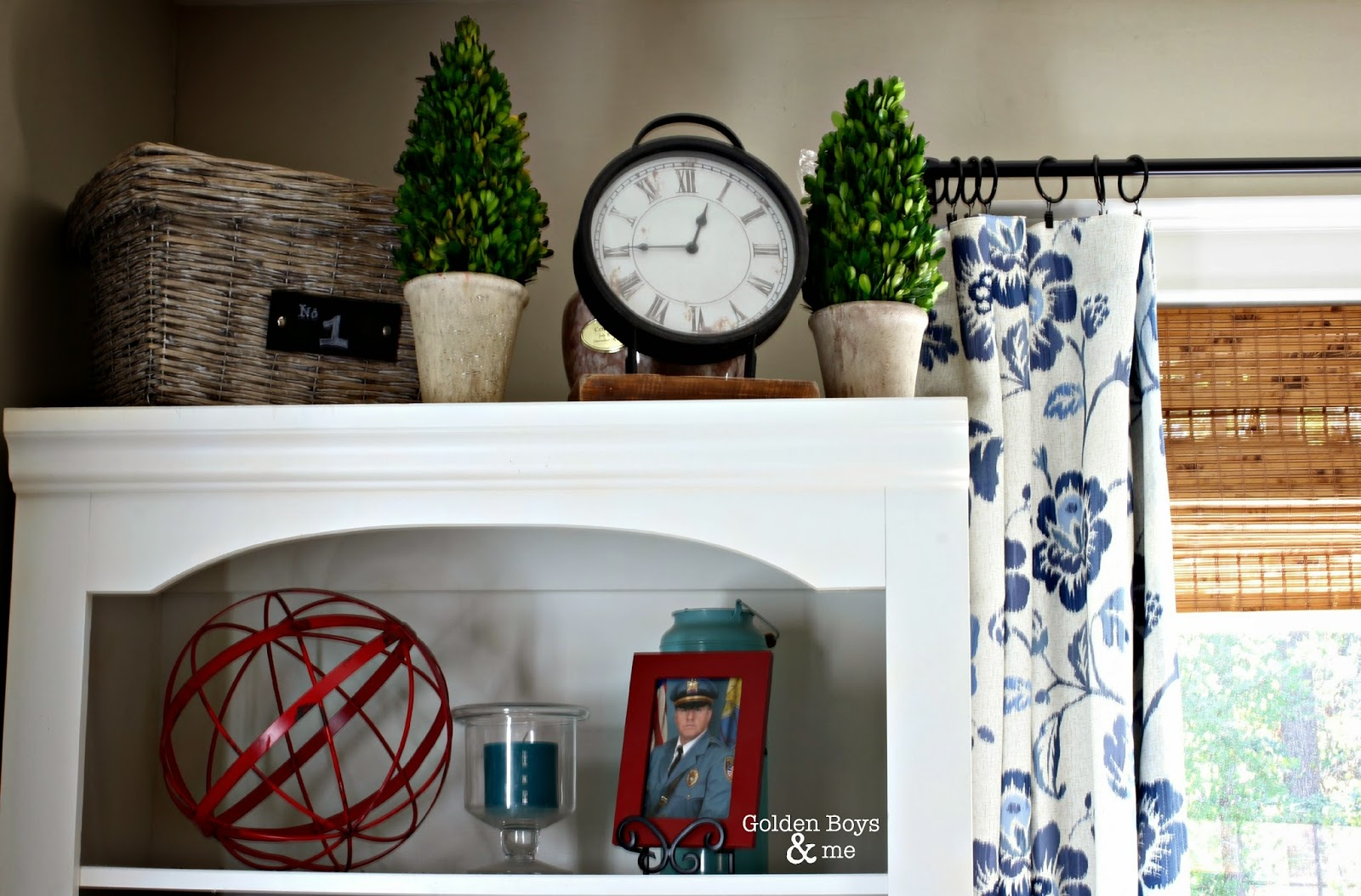 White bookshelf with topiaries, clock and red accents-www.goldenboysandme.com