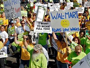 A group of many people standing outside wearing bright yellow or lime green t-shirts, many holding signs. One of the prominent signs has a yellow frowny face in the middle and says Walmart, Always Low Wages